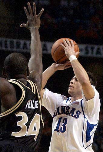 Ku's Jeff Boschee (13) triggers over Stephane Pelle.