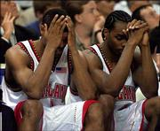 Maryland's Byron Mouton, left, and Chris Wilcox sit on the bench during the final minute of the Terps' loss to N.C. State. The Wolfpack won the ACC semifinal Saturday at Charlotte, N.C.