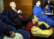 KU coach Roy Williams, upper left, and Jayhawks Lewis Harrison, lower left, Drew Gooden, lower right, and Jeff Carey watch the NCAA selection show Sunday at Kemper Arena.