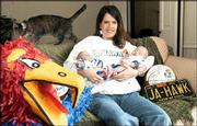 Julie Ann Hawk Goeser, Overland Park, remembers always being called J. Hawk growing up. A true crimson-and-blue supporter, she had a JA-HAWK Missouri license plate through high school and graduated from KU in 1993. Wednesday at her home, Julie holds her newborn Baby Jays, twin daughters Madison, left, and Morgan. Their cat Tabby is in the background.