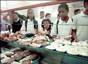 Young boys and girls stand in line to receive their lunches at Jefferson Middle School cafeteria in Long Beach, Calif. One of every five children who gets free or discounted meals at school may be ineligible for them because their family income is too high, according to a government study.