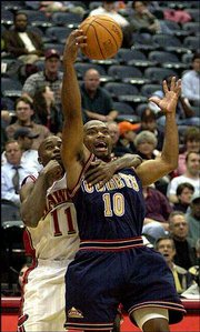 Atlanta's Jacque Vaughn, left, grabs Denver's Tim Hardaway while trying to reach the basketball. Vaughn scored 11 points in the Hawks' 105-102 victory Wednesday night in Atlanta.