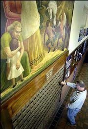 Subjects in a mural painted by Kenneth Evett look over an unidentified man checking his post office box in the U.S. Post Office in Horton.