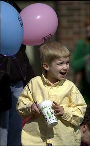Curtis Zicker, age 5, Lawrence, clutches a Free State balloon and a cup he received from a passing float as he cheers for an upcoming entry.