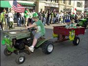 Kirby Wolfe, age 9, pulls his little brother Riley, 7, in an entry that displayed both Irish and American spirit. American flags and patriotic themes were prevalent throughout Sunday's St. Patrick's Day Parade.