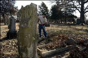 Mitch Young, supervisor at Oak Hill Cemetery, 1605 Oak Hill, tidies up around the grave of Lucy Hobbs Taylor, the first women to graduate from dental college who then came to Lawrence to start a practice.