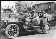 "A car load of suffragists in the early 20th century in Lawrence carry ""Vote for Women"" signs and American flags."