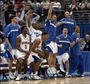 The KU bench celebrates a second-half play.