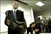 New Texas Christian coach Neil Dougherty smiles after he was presented with cowboy boots during a news conference while his wife, Patti, seated, looks on. Dougherty, a Kansas assistant, was introduced as Billy Tubbs' replacement Monday in Fort Worth, Texas.