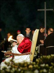 Pope John Paul II attends the Via Crucis (Way of the Cross) torchlight procession on Good Friday in front of the Colosseum in Rome. The pontiff did not walk the half-mile route in the rite that evokes Christ's suffering and death.
