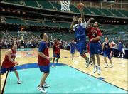 Kansas' Drew Gooden soars to the goal ahead of Todd Kappelmann (50). KU held an hour-long practice Friday at the Georgia Dome.