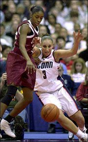 Oklahoma's Dionnah Jackson, left and Connecticut's Diana Taurasi (3) battle for the ball.