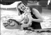 The big water snake is not a threat to little Ashlyn Pope, 13 months, as she plays with her mother, Michelle, at the Lawrence Indoor Aquatic Center's interactive children's pool. The $9.3 million, 850,000-gallon center at 4706 Overland Drive, adjacent to Free State High School, opened last summer.