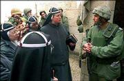Nuns carrying a statue of Mary and baby Jesus speak with Israeli soldiers at Saint Mary's church in the West Bank town of Bethlehem. In the biblical town Thursday, a standoff between Israeli forces and more than 200 gunmen holed up in the Church of the Nativity entered a third day.