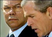Secretary of State Colin Powell, who will travel to the Middle East next week, listens as President Bush makes a statement in the Rose Garden of the White House.
