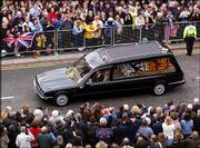 The hearse carrying the coffin of Queen Elizabeth, the Queen Mother, strewn with flowers thrown by members of the public, arrives at Windsor Castle following her funeral service at Westminster Abbey. The queen mother was buried Tuesday next to her husband, George VI, in St. George's Chapel at the castle.