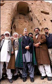 Interim Afghan leader Hamid Karzai, center, poses with unidentified local leaders in front of a destroyed Buddha statue in Bamiyan, central Afghanistan. Karzai said Tuesday that his government will rebuild giant statues of Buddha that were destroyed by the Taliban last year.