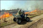 Roger Boyd, a Baker University professor of biology and caretaker of the Baker Wetlands, watches a fire burn in the wetlands. The exercise Tuesday was part of an every-other-year rite to rid the area of trees, shrubs and sunflowers and generate new prairie grass growth.