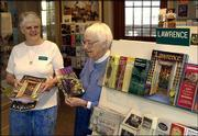 The Lawrence Visitor's Center, with volunteers like Judy Henderson, left, and Bunny Richards, offers a variety of local and regional travel and tourism materials at the Union Pacific Depot. Lawrence's annual tourism report reflected a decrease in visitors and in money added to the local economy.