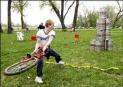 Kyle Batton, Lawrence, tries his best to knock down a tower of beer kegs with a beat-up bicycle. The event was part of the annual Tour De Fat Saturday at Burcham Park.