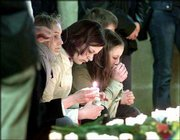 Unidentified girls grieve for the victims of a Friday school shooting in the Cathedral of Erfurt, Germany. Stories about the shooting, in which 16 people were killed one fewer than originally thought began to come into focus Saturday.