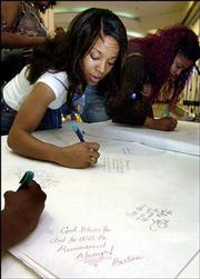 "Jada Holmes, left, and Ginger Sherrell sign a sympathy card for hip-hop star Lisa ""Left Eye"" Lopes. A member of the trio TLC, Lopes was killed Thursday night in a traffic accident in Honduras. Fans signed the card Saturday at a mall in Atlanta, Lopes&squot; hometown."