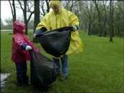 A steady rain doesn't keep members of the Murphy family of Lawrence from participating in the 19th annual Clinton Lake Cleanup. Hannah Murphy, 6, and her mother, Mary Murphy, searched for litter Saturday around a Clinton Lake picnic area.