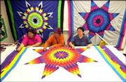 From left, Kepsey Fixico and Faye Baker, both of the Muskogee Creek Nation, and Marilyn Thunder Hawk, of the Sicangu Lakota Tribe, handstitch a fire-colored star quilt. The three Lawrence residents are part of Piece by Piece, a group that uses quilting to share skills and oral traditions with young people. The quilters, who mainly use donated materials, are preparing to show their work to the public May 9-10 at Osceola-Keokuk Hall at Haskell Indian Nations University.