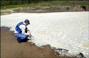 DAVE MURPHY, director of Kansas Riverkeeper, finds an area of the river totally engulfed by foam that he says is caused by organic waste.