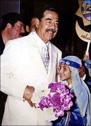 Iraqi President Saddam Hussein accepts a bouquet of flowers during a celebration of his birthday at the presidential palace in Baghdad. Saddam turned 65 Sunday.