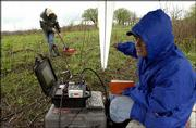 Kimberly Henderson, foreground right, a graduate student at University of Denver, monitors the visual display of a ground-penetrating radar system, while workers in the background pass radar antennas over plotted grids in the Baker Wetlands area. Geophysical Investigations Inc., Lakewood, Co., will search a number of sites for evidence of graves.