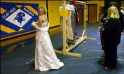 Samantha Cummings, 15, left, a freshman at Clay County High School, checks the length of a donated prom dress as her teachers Dana Remias and Christine Walker look on recently in Clay, W.Va. Students at a $20,000-a-year girls school in New York City donated about 450 gowns to girls in the West Virginia area.