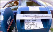 A motorist drives away from taped-off mailboxes at the U.S. post office in Moline, Ill., Friday, May 3, 2002. Pipe bombs accompanied by anti-government propaganda exploded Friday in six mailboxes in rural parts of Illinois and Iowa, an attack authorities called domestic terrorism.
