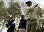Gale Sayers takes a practice swing during the Gale Sayers golf tournament. The benefit raised about $15,000 for scholarships for KU's School of Education on Friday at Alvamar. From left are Sayers' former teammate, Mike Wolf, and Wayne Osness, who was Sayers' adviser at KU.