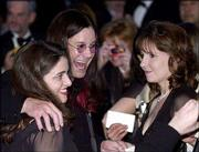 Rocker Ozzy Osbourne, center, poses for a picture with unidentified participants during the annual White House Correspondents Assn. Dinner in Washington. Osbourne was a guest of Fox News' Greta Van Susteren.