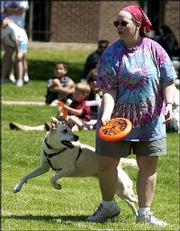 Traci Fullerton, Lawrence, competes in the flying-disc competition with her dog, Beth. Twenty dogs and their owners competed Sunday in the competition in conjunction with Art in the Park at South Park.
