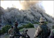 British soldiers look on as ordnance are destroyed near one of the caves in Paktia Province, southeastern Afghanistan. British troops on Friday destroyed several caves housing tens of thousands of rockets, shells and grenades that once belonged to the Taliban.