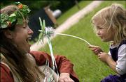 Bridesmaid Diana Schmitt, Swannanoa, N.C., and her daughter Cyrus McCall, 2, play with a dragonfly wand after a Renaissance-themed wedding ceremony at Clinton Lake's Bloomington Park. Saturday's wedding featured handmade costumes and a seven-course feast.