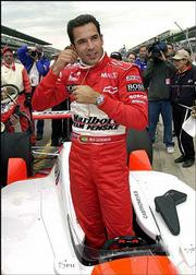 Defending Indy 500 champion Helio Castroneves, of Brazil, climbs out of his car following his qualification run. Castroneves qualified with an average speed of 228.906 mph Saturday at the Indianapolis Motor Speedway.