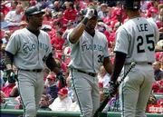 Florida's Cliff Floyd, center, accepts congratulations from teammates Preston Wilson, left, and Derrek Lee after hitting a home run in a recent game. Patchwork pitching, dazzling defense and a couple of hot bats have carried the Marlins to first place in the National League East.