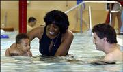 Charlene and Justin Palmer watch as their son, Wesley, 6 months, gets his first-ever taste of swimming at the Lawrence Indoor Aquatic Center's children's pool. The family went to the center Sunday afternoon to take advantage of the Mother's Day family special.