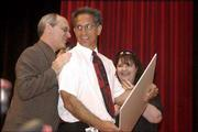 "Lawrence Supt. Randy Weseman, left, gives a pat on the back to Central Junior High School teacher Brian ""Chip"" Anderson during an orchestra concert at the school. Anderson on Thursday was named the Lawrence Schools Foundation ""Bobs&squot; Award"" recipient for 2001-&squot;02. The teaching excellence award carries a $10,000 gift from benefactors, all of which are named Bob. Looking on at right is Anderson&squot;s wife, Vickie."