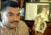 "Orlando Gaitan holds a picture of his mother, Florestella Torres. Wal-Mart received $72,321 in life insurance proceeds when Torres, who worked in the cosmetic department at Wal-Mart, died four years ago. The family has filed a lawsuit against Wal-Mart. Gaitan said ""they shouldn&squot;t have been profiting from my mother&squot;s death."""