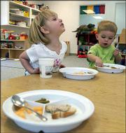 Laurel Bird, left, talks to her friends while Will Cook enjoys his food during lunch at Stepping Stones preschool. Bird is allergic to peanuts, so the preschool has taken them out of the menu.
