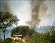 Smoke rises from an area controlled by Pakistan, close to the International border with India. Troops from both sides of the nuclear rivals exchanged heavy fire Saturday, forcing migration of border villagers to safer areas.