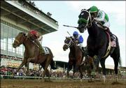 Jockey Victor Espinoza rides War Emblem, right, to victory in the 127th Preakness Stakes. War Emblem held off runner-up Magic Weisner, left, and Proud Citizen, center, to capture the second jewel of horse racing's Triple Crown on Saturday in Baltimore.