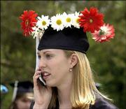Dana Bottenfield, Lawrence, attracts attention with a flower-festooned mortarboard. She was keeping in contact with family members via a cell phone Sunday before she picked up her bachelor's degree in English.