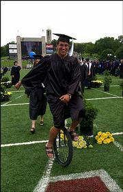 Chris Holzwart, Fort Collins, Colo., opts for alternate transportation to descend down Campanile Hill and into Memorial Stadium. Holzwart and his unicycle were in the procession with members of the College of Liberal Arts and Sciences.