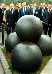 President Bush jokes with Russian President Vladimir Putin, left, as they look at four cannonballs that sit in Cathedral Square in Moscow. The two leaders agreed Friday to cut their nuclear arsenals.