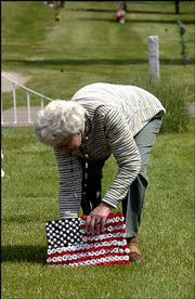 Connie Webb-Smith, Lake Lotawan, Mo., drove to Lawrence, her hometown, to place a flag on her brother's grave in preparation for Memorial Day. Area veterans' groups have planned ceremonies throughout the weekend.